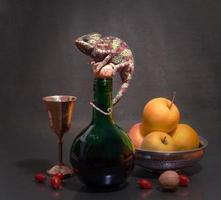 camaleão em uma garrafa com natureza morta de frutas foto