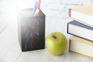 conceito de escola com maçã no bloco de notas na mesa foto