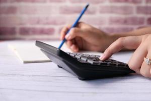 mão usando calculadora na mesa do escritório foto