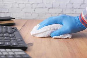 mão limpando a superfície da mesa foto