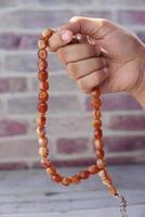 pessoa segurando contas de oração foto