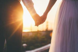 noiva e noivo de mãos dadas ao pôr do sol
