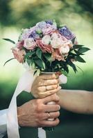noiva e noivo segurando um buquê