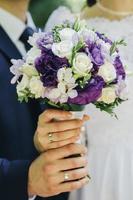 noiva e noivo segurando um buquê branco e roxo