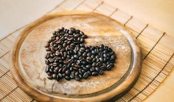 grãos de café em uma placa de madeira em forma de coração foto