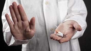 pare de fumar o conceito com um cigarro quebrado nas mãos de um médico foto