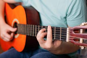 cara toca violão, dedo segura um acorde de compasso foto