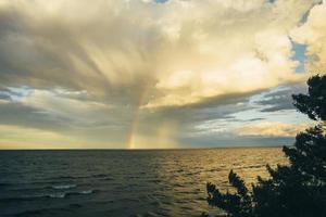 arco-íris no mar através das nuvens foto