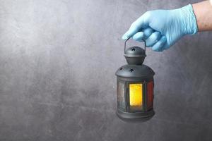 mão segurando uma lanterna em fundo cinza foto