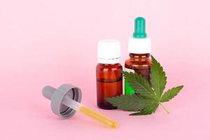 medicamentos de extrato de maconha com folha verde e óleo de cannabis em fundo rosa foto