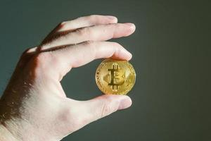 homem segurando bitcoin na mão foto