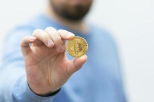 homem segurando bitcoin na mão