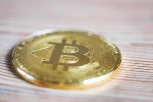 close-up de uma moeda de criptomoeda bitcoin em um fundo de madeira