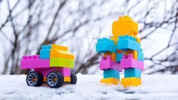 carro de brinquedo de inverno ano novo e robô na neve na rua foto