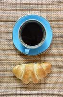 xícara de café e croissant fresco isolado em fundo marrom texturizado vintage. vista de cima no café da manhã fresco com café e bolos doces assados.