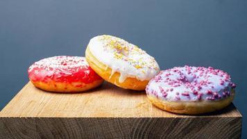 donuts com cobertura multicolorida vermelha, branca e roxa em um suporte de madeira sobre um fundo cinza foto