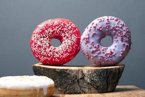 dois donuts coloridos em close-up de toco de madeira foto
