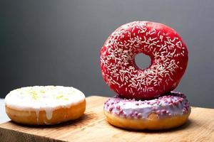 donuts multicoloridos de férias em pó em um suporte de madeira sobre um fundo cinza foto