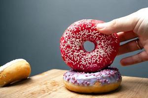 mão feminina segura rosquinhas doces com esmalte vermelho e violeta em um fundo cinza
