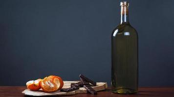 jantar romântico com uma garrafa de vinho com chocolates doces e tangerinas foto