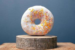 donut com glacê branco e pó colorido em um suporte de madeira e fundo cinza