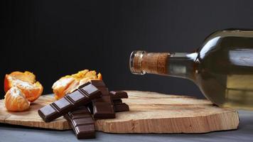 garrafa de vinho branco com chocolate ao leite e tangerina em um suporte de madeira foto
