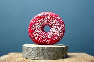 donut com esmalte vermelho e pó branco em um suporte de madeira sobre um fundo cinza