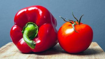 tomate e pimentão vermelho doce em uma placa de madeira sobre um fundo cinza foto