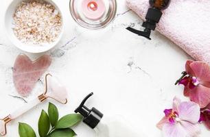 massagem facial rolo jade com produto cosmético em fundo de mármore foto