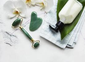 massagem facial rolo jade com produto cosmético em fundo de mármore
