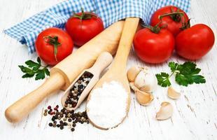 tomate, alho e farinha em um fundo de madeira