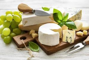 vários tipos de queijo em um fundo branco de madeira