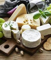 vários tipos de queijo, uvas e vinho em uma mesa de madeira