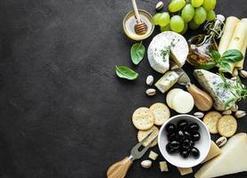 vários tipos de queijo, uvas, mel e salgadinhos em um fundo de concreto preto