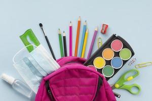 máscara e material escolar na mochila rosa