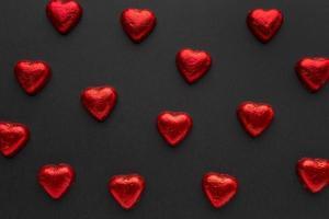 corações de chocolate vermelho dispostos em fundo preto