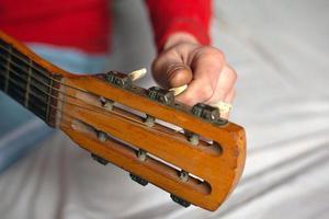 mão do músico torce as melodias do violão, afinando o instrumento foto
