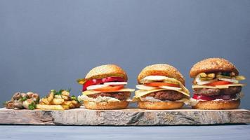 hambúrgueres suculentos com batatas fritas e cogumelos em um prato de madeira foto