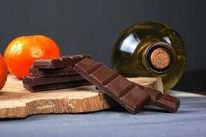 garrafa de vinho branco com pedaços de chocolate ao leite e tangerinas em uma prateleira de madeira da floresta foto