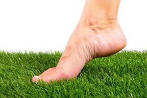 pé descalço tocando grama artificial verde em um fundo branco foto