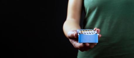 pessoa oferece fumar, maço de cigarros na mão em um fundo escuro com espaço de cópia foto