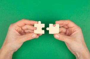 peças do puzzle nas mãos sobre um fundo verde foto
