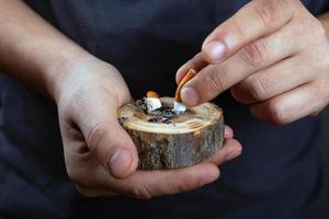 mãos masculinas apagando a bituca de um cigarro em um suporte de madeira na floresta