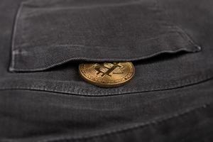 moeda bitcoin de metal no bolso da calça foto