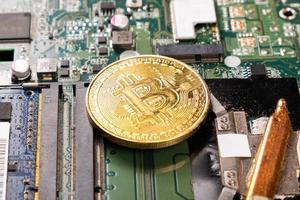bitcoin de moeda de ouro em uma placa de computador, conceito de mineração, criptomoeda foto