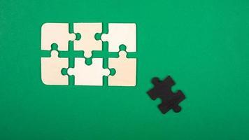 peças do quebra-cabeça, cores branco e preto sobre fundo verde foto
