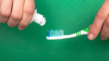 mão espremendo pasta de dente em uma escova de dente em um close-up de fundo verde foto
