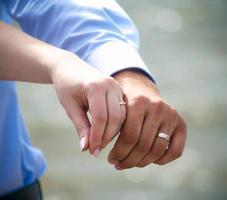 casal mostrando alianças de casamento foto