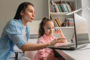 pai configurando escola virtual no laptop para a filha