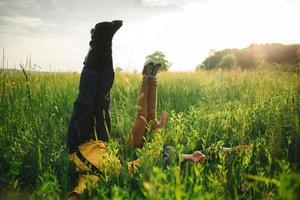 menino com menina em um campo deitado na grama verde com pernas e mãos para cima. foto
